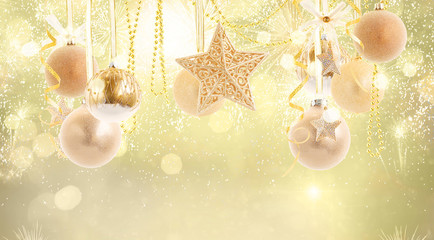 Hanging golden christmas balls row on golden bokeh background with copy space