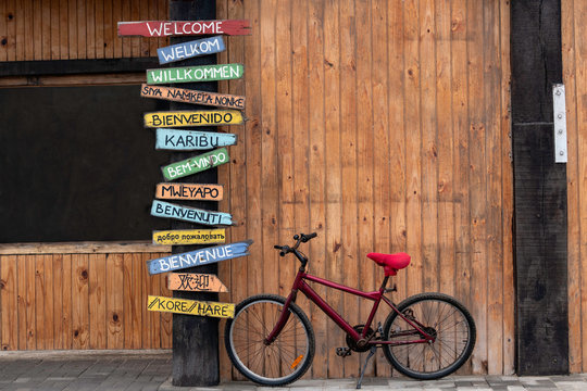 Red Bike Next to a Post with Welcome Signs in Several Different Languages.  English, Afrikaans, German, Xhosa, Spanish, Swahili, Portuguese, Oshiwambo, Italian, Russian, French, Japanese, Korean