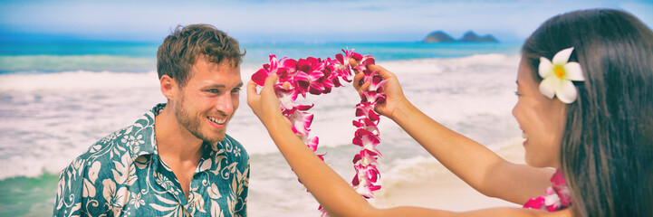 Hawaii woman giving lei flower garland welcoming tourist man on Hawaiian beach. Portrait of a Polynesian culture tradition of giving a flower necklace to a guest as a welcome gesture. Banner panorama.