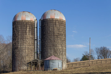 Two old concrete grain silos on a hillside, blue sky winter, horizontal aspect