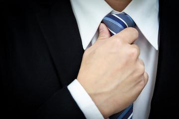 Portrait of business man adjusting his necktie close up.