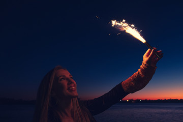 Overhappy woman holding burning roman candle in her raised hand