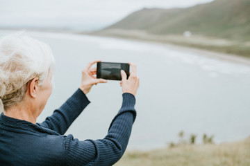 Elderly woman capturing a photo of the ocean