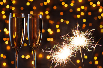 Glasses of champagne and Sparkler on the background of a garland at Christmas.  New year's eve together