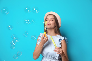 Young woman blowing soap bubbles on color background