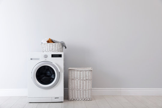 Washing machine with laundry and basket near wall. Space for text