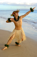Male Hula Dancer performing on the sand next to the ocean.
