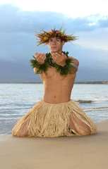 Male Hula Dancer kneels in a pose of worship.