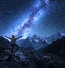 Silhouette of a standing man with raised up arms on the stone, mountains and starry sky with Milky Way at night in Nepal. Sky with stars. Travel. landscape with mountain ridge and milky way. Space