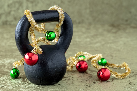 Black kettlebell on a green velvet background with green and red ball ornaments on a gold garland, holiday fitness