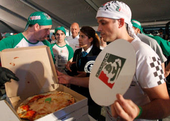 An official from Guinness records checks pizzas cooked by Argentine chefs in an attempt to enter the Guinness World Records for the largest number of pizzas prepared in 12 hours by a team, in Buenos Aires