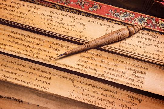 pen for writing text on Bai Lan background, Bai Lan or ancient palm leaf manuscripts content about buddhist scriptures, Pali language Khmer