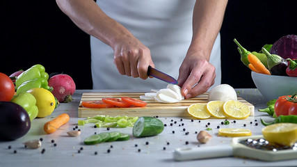 Man is cutting vegetables in the kitchen, slicing black radish