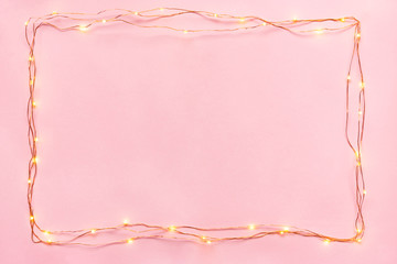 Christmas lights garland border over pink background. Flat lay, copy space.