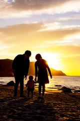 夕陽の沈む海岸と家族のシルエット