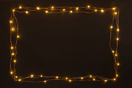 Christmas lights garland border over black background. Flat lay, copy space.