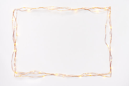 Christmas lights garland border over white background. Flat lay, copy space.