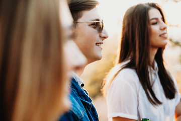 Side view of attractive guy in stylish glasses smiling and looking away while standing in countryside near female friends. Smiling man near friends in nature