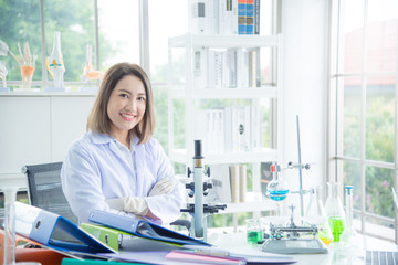 Beautiful asian scientist in white coat sitting in lab and smile at camera