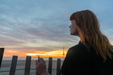 Ginger girl with blue eyes looking over a fence in the beach watcihng the sunset