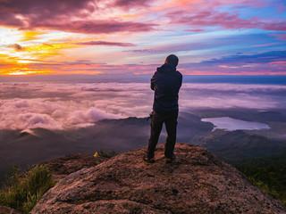 "Traveler stand on Rocky cilff with sunsire sky and beautiful cloud sea on ""Pa na rai"" Khao Luang mountian Ramkhamhaeng National Park,Sukhothai Province thailand"
