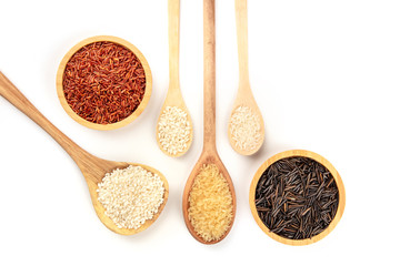 Various types of rice, shot from above on a white background with a place for text. White, red, brown and black rices in wooden spoons and bowls with copy space