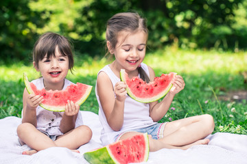 two little cute girls eating watermelon outdoors