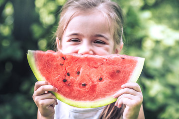 a little girl holding a piece of watermelon