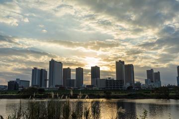 the sun sets in the buildings across the Tama River Kawasaki Kanagawa Japan