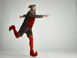 friendly man dressed like a funny gnome posing on an isolated gray background