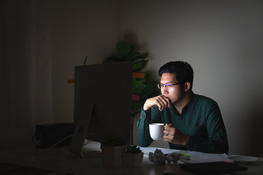 Attractive young asian man drinking coffee sitting on desk table looking at laptop computer in dark late night working feeling serious thinking and determinated at home office in work hard concept.