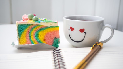 Rainbow Cake cream and book, pen, mobile are placed on a white background.