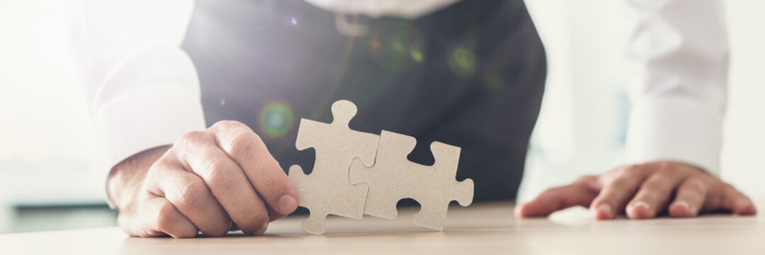 Wide view image of a businessman holding two puzzle pieces matched together