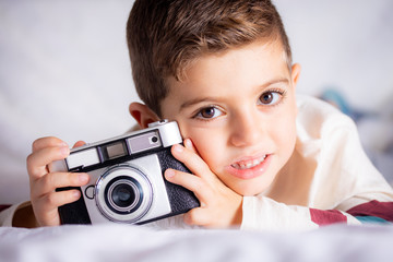 Beautiful boy with a photographing camera in the bed