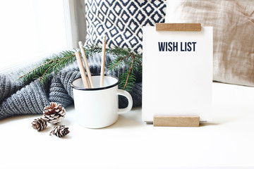 Winter desktop still life scene. Wish list card, board and wooden pencils in mug standing near window on white table background. Christmas concept. Pine cones and fir branch on wool plaid.