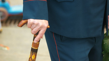 Old military man with a walking cane. Close up hand of an elderly War veteran using walking stick outdoors. Day of Victory.