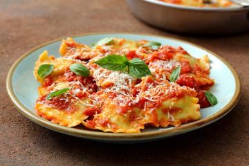 Pasta Italiana ravioli ripieni con salsa di pomodoro e parmigiano su tavolo di cucina,