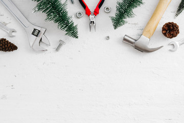Merry Christmas and Happy new year handy tools and Christmas ornaments decoration on grunge white wood background concept. Top view with copy space.