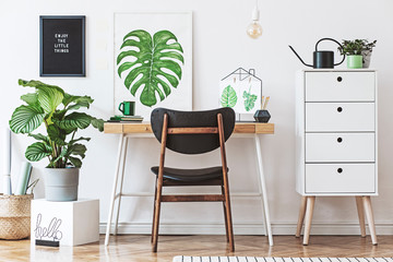 Stylish scandinavian home office desk with mock up poster frames, a lot of plants and office accessories. Brown wooden parquet and white backgrounds wall. Modern composition of homeoffice desk.