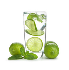 Glass of water with lime and mint on white background