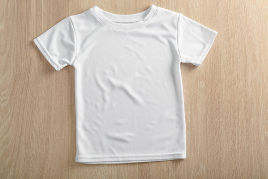 White t-shirt on wooden background, top view