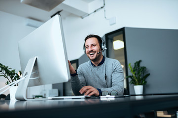 Low angle image of happy casual businessman working on computer with headset.