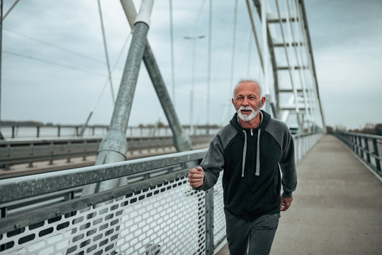 Portrait of older male runner running outside.