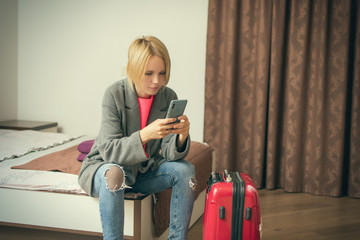 A woman is sitting with a phone on the bed near the suitcase.
