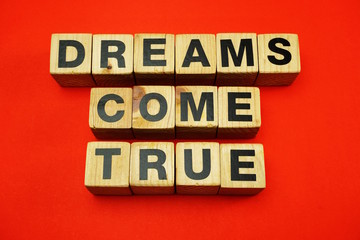 dream come true word created with cubes alphabet letters on red background