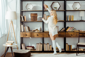 beautiful adult woman taking book from wooden rack