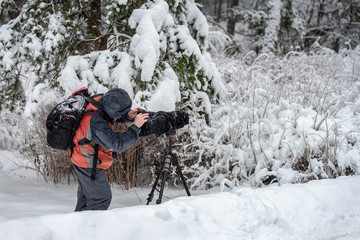 Behind the scene. Cameraman with video camera on tripod, shooting the film scene at outdoor location, on nature, forest, cold winter snowy day