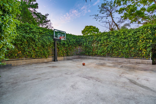 Empty private concrete basketball court with basketball surrounded by green hedges during a pastel sunset.