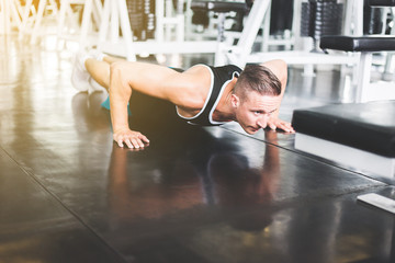 Strong caucasian man doing push up and exercises on floor at gym
