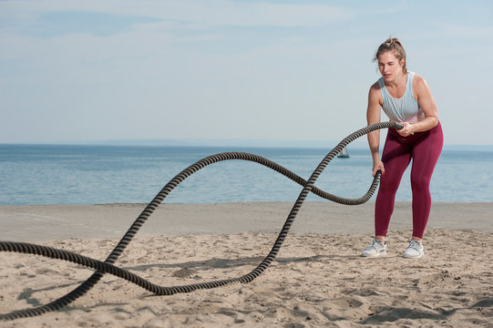 Young attractive sportive woman battling ropes doing a workout exercise on a beach. Sportive woman in pink leggings doing workout using ropes at the seaside.